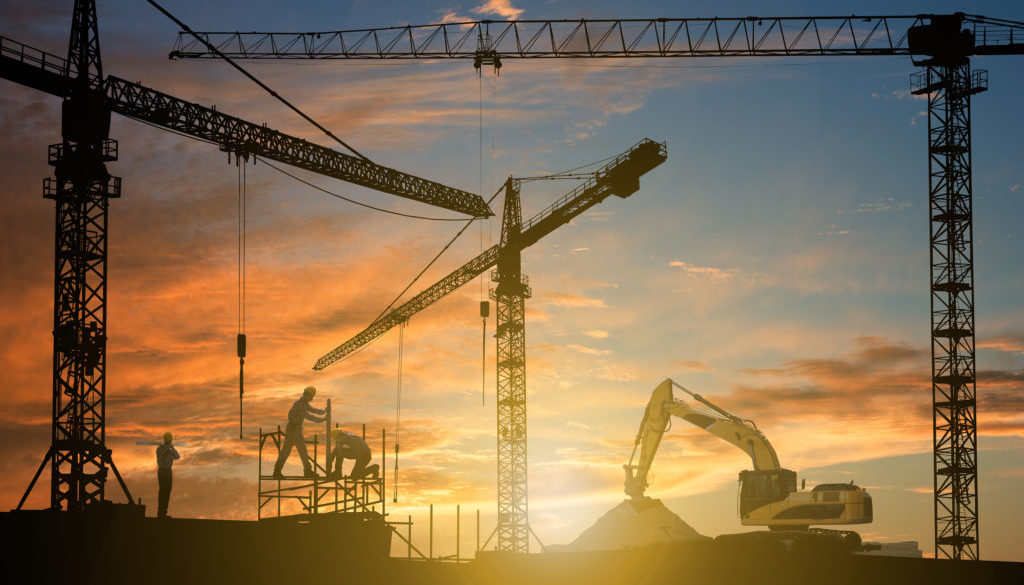 People At Construction Site With Cranes During Sunset